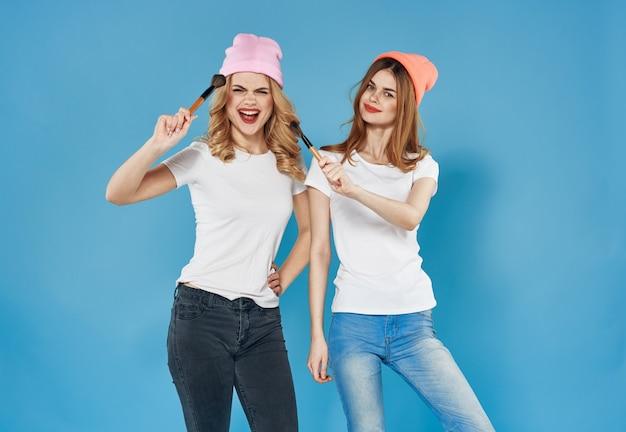 ファッショナブルな服の化粧品の週末の楽しいライフスタイルの青い壁の2人のガールフレンド。