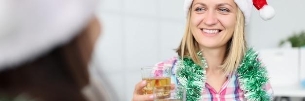 サンタクロースの帽子をかぶった2人のガールフレンドは、手に飲み物を持って眼鏡を持っています