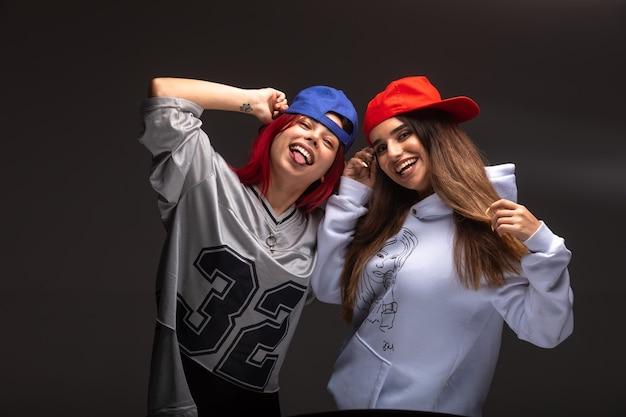 Две подруги в спортивных костюмах веселятся.