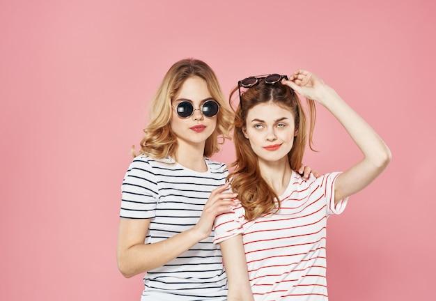 ストライプのtシャツメガネの2人のガールフレンドは、贅沢なライフスタイルをファッションします。高品質の写真