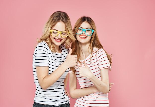 Две подруги в полосатых футболках в очках, мода, веселый образ жизни, изолированный фон