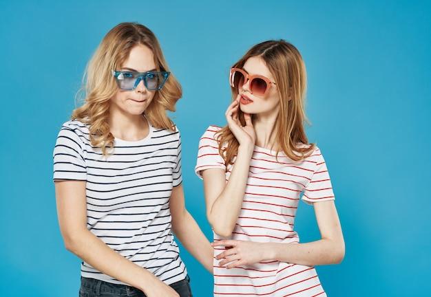 ストライプのtシャツサングラスコミュニケーションスタジオの楽しみの2人のガールフレンド