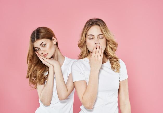 Две подруги в белых футболках устали смотреть отпуск образ жизни розовый фон. фото высокого качества