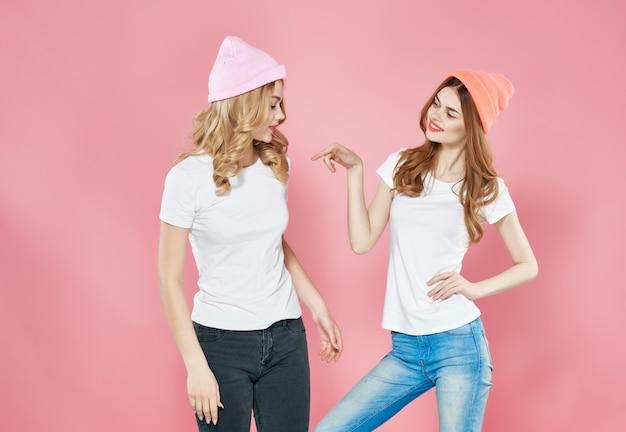 白いtシャツの感情の楽しいファッショングラマーの2人のガールフレンド