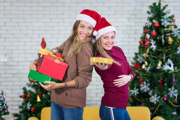 笑ってクリスマスプレゼントを共有する2人のガールフレンド。クリスマスのお祝いと新年のパーティー