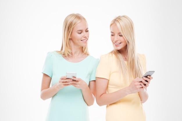 彼らの電話を見ている2人のガールフレンド。白い壁に隔離