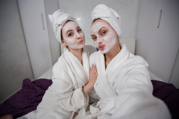 Two girlfriends make funny faces stretch their lips while taking selfies in bathrobes and moisturizing face masks high quality photo