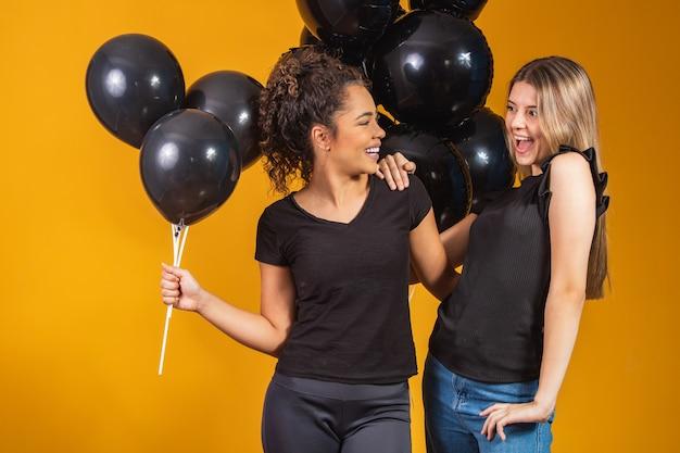 검은 금요일 프로모션 파티에서 검은 풍선과 함께 노란색 배경에 두 여자 친구.