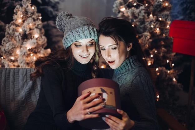 Две подруги, открывающие коробку с подарком в рождественскую ночь.