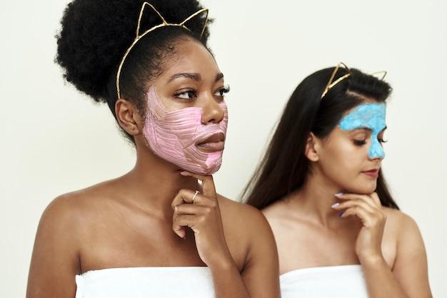 恋をしている2人のガールフレンドまたは若い女性は、自分でマルチマスキングを試みます。