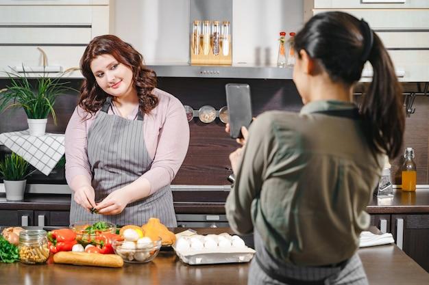 두 여자 친구는 소셜 네트워크를 위해 스마트폰으로 비디오를 녹화하거나 사진을 찍고 있습니다. 플러스 사이즈 여성 블로거는 주방에서 다이어트와 건강식에 대한 블로그 콘텐츠를 만들고 있습니다.
