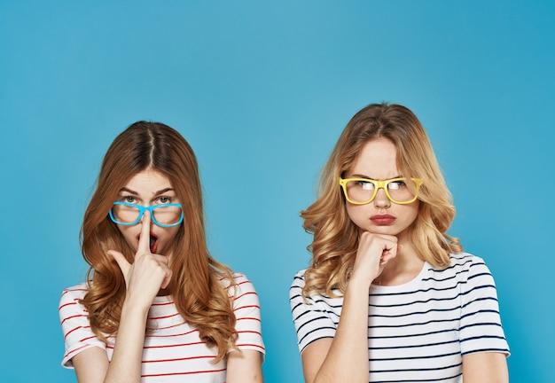 ファッションスタジオのライフスタイルを社交する2人のガールフレンドは、青い背景をトリミングしました。高品質の写真