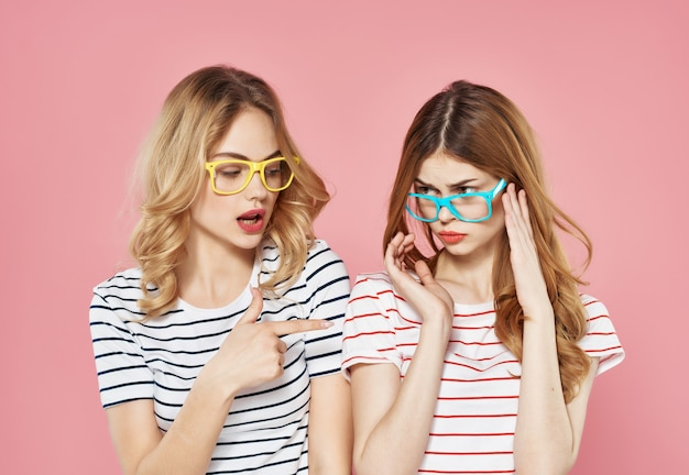 Two girlfriends stand side by side in striped tshirts glasses fashion summer pink background