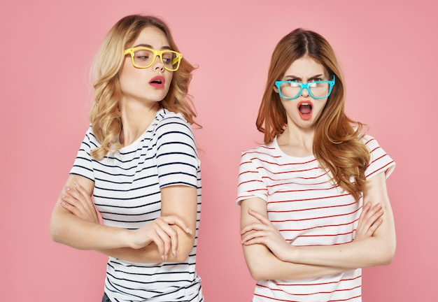Two girlfriends striped tshirts with sunglasses pink background