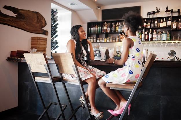 Two girlfriends at summer dresses drinking milkshake cocktails in bar