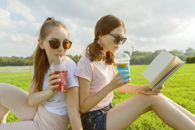 Two girlfriends teenagers sit on green lawn