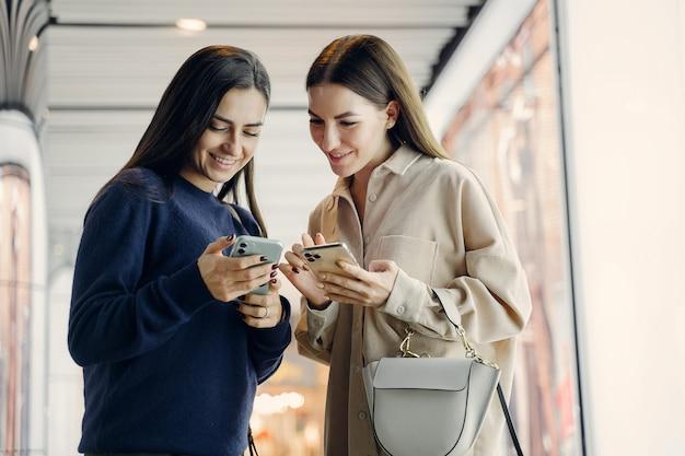 夜に新しい街を探索しながら携帯電話を使用して2つのガールフレンド