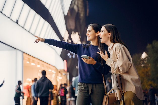 밤에 새로운 도시를 탐험하면서 핸드폰을 사용하는 두 여자 친구
