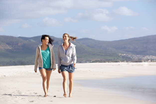 Two girlfriends walking and talking on the beach