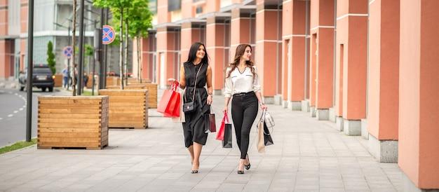 Две подруги гуляют по улице с сумками возле торгового центра