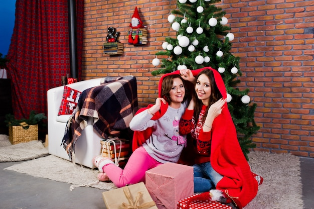 Two girlfriends wear on winter sweaters sitting at room with chrismas decorations.