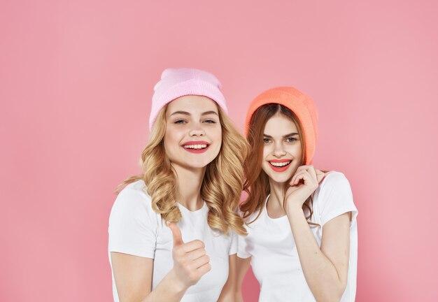帽子をかぶった2人のガールフレンドモダンなスタイルの友情ファッション孤立した背景