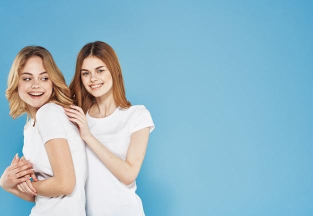 두 여자 친구 흰색 티셔츠 포옹 라이프 스타일 블루 스튜디오 배경. 고품질 사진