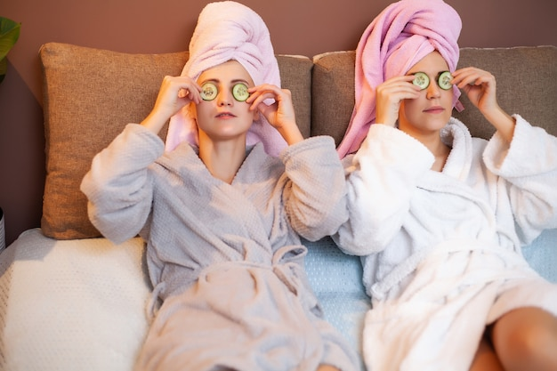 Two girlfriends with towels on their heads, doing spa treatments at home in bed