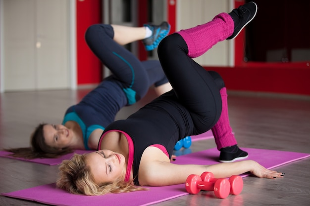 Two girls do aerobics exercises on mats in fitness center