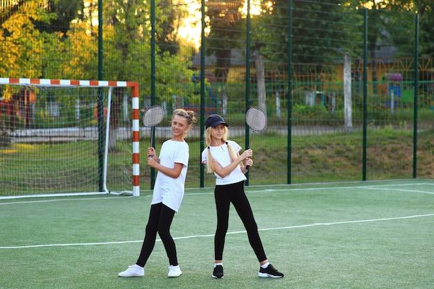 수업을 마치고 두 소녀가 놀이터에서 테니스를 치러갑니다.