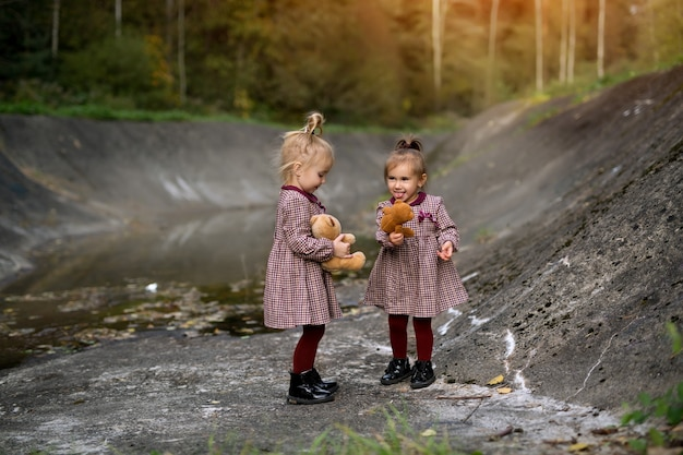 동화 숲의 회색 바위 슬로프 사이에 있는 두 소녀는 테디베어를 손에 들고 있다
