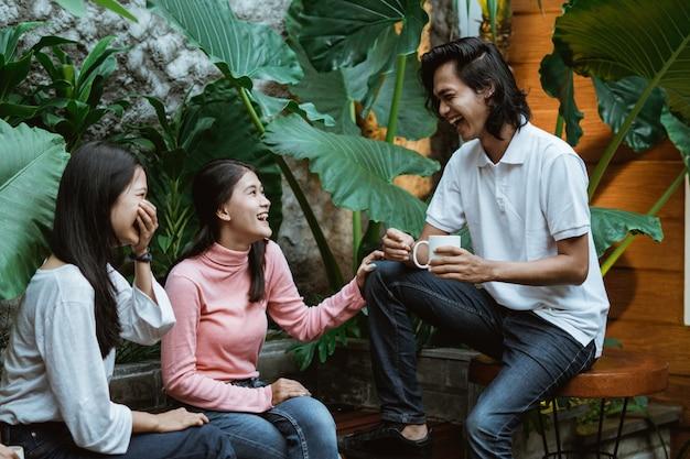 두 소녀와 소년은 나무 의자에 앉아 컵을 들고 정원에서 유쾌하게 웃고 있습니다.