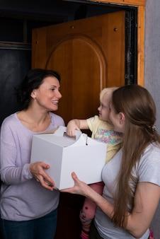 ボックスにケーキを持つ2人の女の子と子供。お母さんが娘を訪ねてきました。