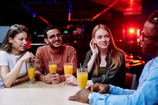 Две девушки и парень слушают, как их друг рассказывает им о себе у стакана сока в баре