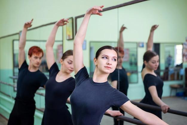두 소녀와 한 소년은 큰 거울 근처 스튜디오에서 발레를 연습합니다