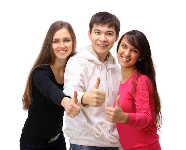 Две девушки и один парень показывают палец вверх. изолированные на белом