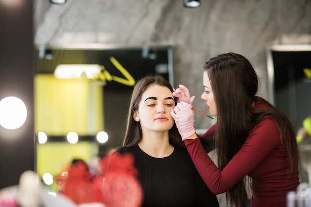 Two girls are doing make-up in front of big mirror