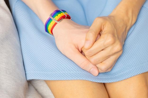 2人の女の子が手をつないでいます。一方でlgbtブレスレットがあります。愛、性的寛容、同性愛の概念。