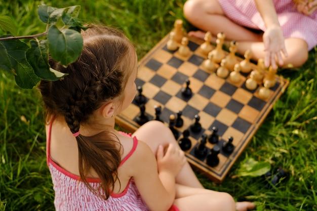 Две девушки играют в шахматы на деревянной шахматной доске на открытом воздухе на природе
