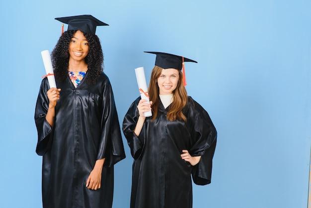 Две девушки позируют для фото в черных платьях и держат диплом. они выпускники и имеют диплом. они счастливы и в хорошем настроении.