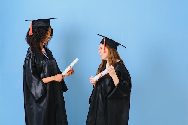 Две девушки позируют для фото в черных платьях и держат диплом.
