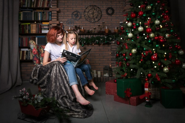 Two girls are reading a book in an armchair. christmas tree. the room is decorated for christmas.