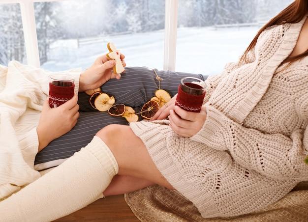二人の女の子が窓の近くに座ってお茶を飲んでいます