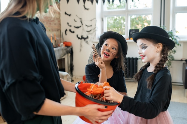 Two girls asking young woman in black attire for halloween treats