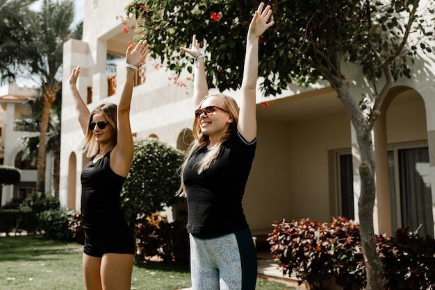 두 여자 선수는 집 근처 잔디밭에서 스트레칭