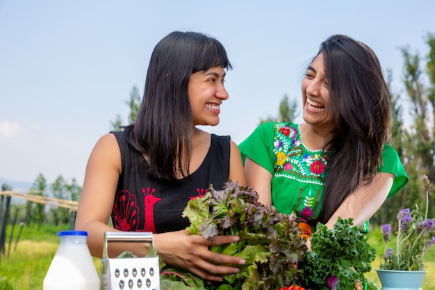 Two girls and basket of fresh vegetables