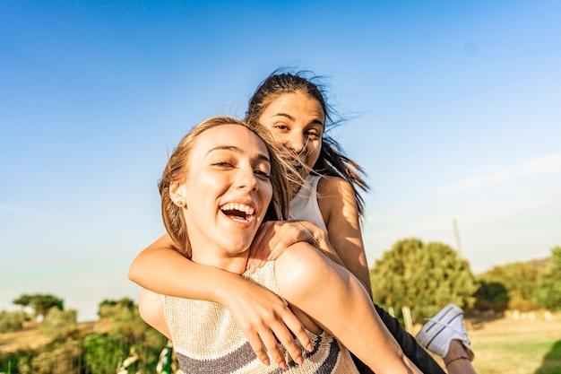 웃으면서 농담을 하는 녹색 자연 공원에서 야외에서 즐거운 시간을 보내는 두 여자의 가장 친한 친구