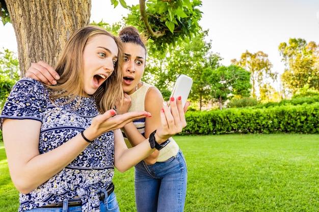 2人の女の子の親友は、不信のしかめっ面と大きく開いた口と目を驚かせてスマートフォンに驚いています都市公園でソーシャルネットワークを楽しんでいるテクノロジーを楽しんでいる若い女性のカップル