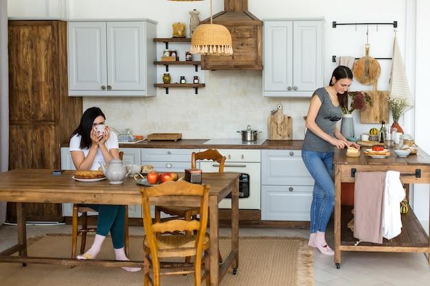 Две девушки-брюнетки пьют чай с тортом и сладостями за столом. фото высокого качества
