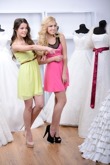 Two girls came to the wedding dress shop.